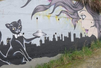 Wall mural showing a black cat holding a flying saucer out to a woman's head.
