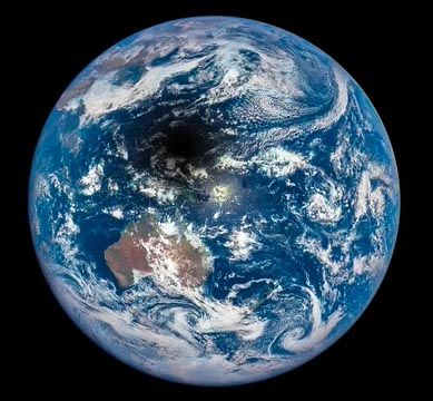 A photograph of Earth from space showing the moon's dark shadow