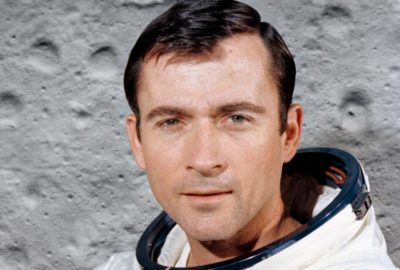 Astronaut John Young in front of a lunar surface image