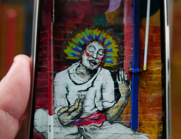 Augmented Reality Mural of a Woman wearing white, painted on a red brick wall augmented with flowing rainbow hair
